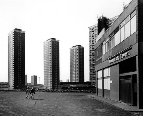 Wohnblock in Glasgow mit IRA-Graffito. In den 1960ger Jahren wurden in Glasgow und Vororten zahllose neue Wohnungen für die Menschen, die bisher unter unzumutbaren Zuständen in der Innenstadt gehaust hatten. Zwei Jahrzehnte später sind auch diese Wohnblocks verwahrlost. Die  Menschen in Glasgow, besonders die in Schwer- und Schiffbauindustrie, litten in den 1980ger Jahren sehr unter dem Rückgang ihrer Branchen. Arbeitslosigkeit, Armut, Alkohol- und Drogenmissbrauch waren die Folge. Religiöse Fanatisten machten sich die Situation zunutze.  | Tenement building with IRA-Graffiti.