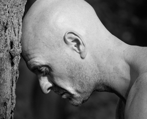 Profilfotografie eines glatzköpfigen Mannes mit freiem Oberkörper, der seinen Kopf gegen einen Baumstamm gelehnt hat.